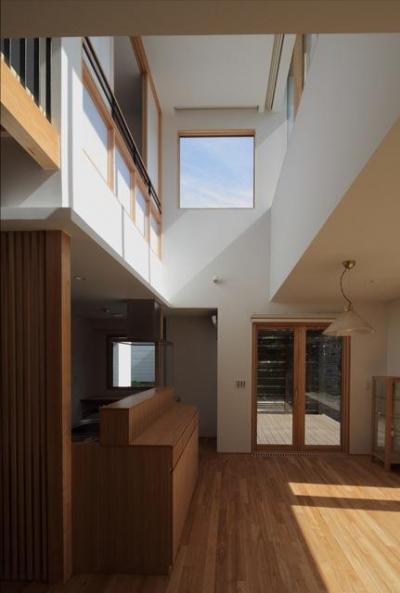 『銭函 光庭の家』質感の深みが感じられるシンプルな住まい (吹き抜けのダイニングキッチン)