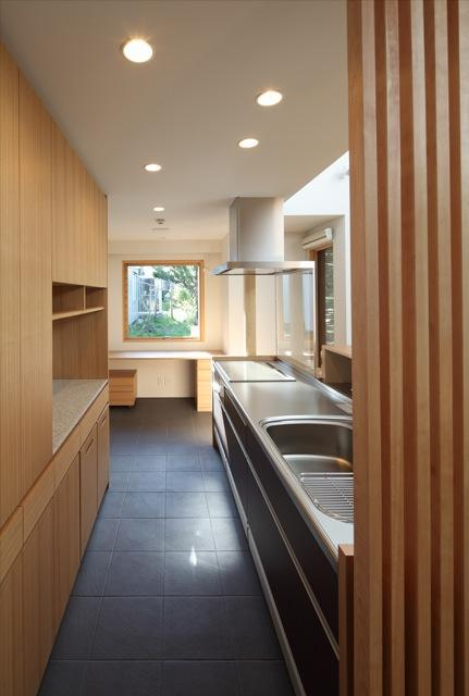 『銭函 光庭の家』質感の深みが感じられるシンプルな住まいの部屋 ピクチャーウィンドウのあるキッチン