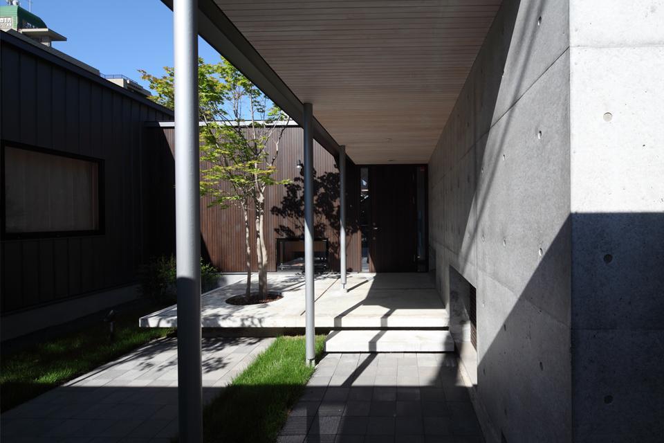 『マロニエ通りの家』家族を心地よく、緩やかにつなぐ二世帯住宅の部屋 中庭を通るアプローチ