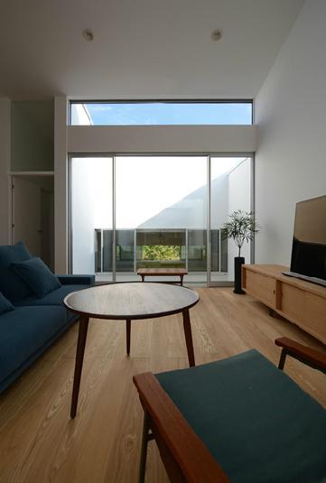 『YM-house』光と風を採り込む方流れ屋根の家の部屋 リビングよりライトコートを見る