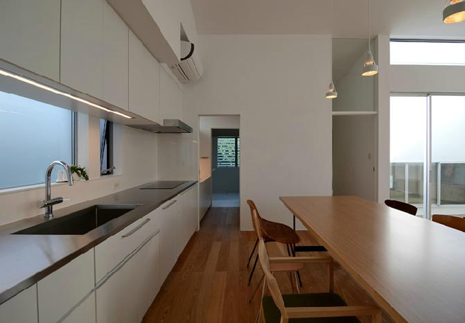 『YM-house』光と風を採り込む方流れ屋根の家の部屋 ダイニングキッチン-奥は洗面室