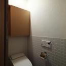 『AR-house』敷地段差を活かした2世帯住宅の写真 白いタイル壁のトイレ
