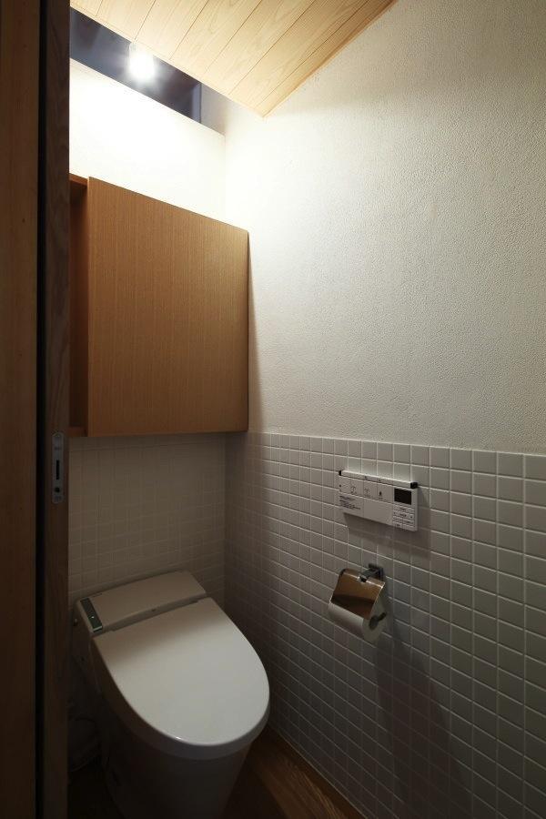 『AR-house』敷地段差を活かした2世帯住宅の部屋 白いタイル壁のトイレ