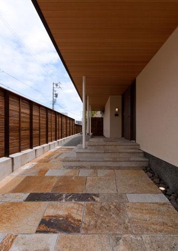 『名古屋のコートハウス』バーベキューテラスのある家の部屋 天然石貼りのアプローチ