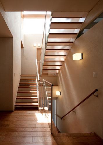 『名古屋のコートハウス』バーベキューテラスのある家の部屋 ハイサイドライトより光が降り注ぐ階段室