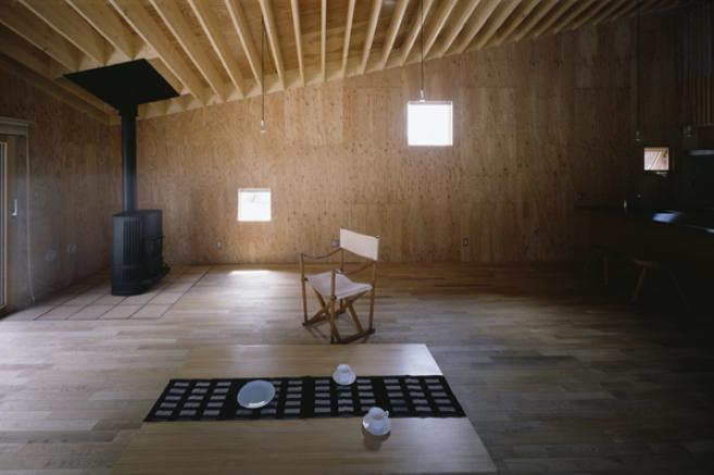 『蘭島のCOTTAGE』木に囲まれた海沿いの別荘の部屋 薪ストーブのあるリビング