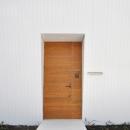 白い外壁に映える木製玄関ドア