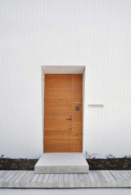 『富木島の家』クール&斬新デザインの都会的な住まいの部屋 白い外壁に映える木製玄関ドア