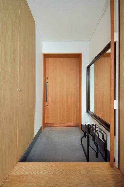 『小さな平屋』内部と外部の関係性を見出すFRPグレーチングの写真 木製引き戸の玄関