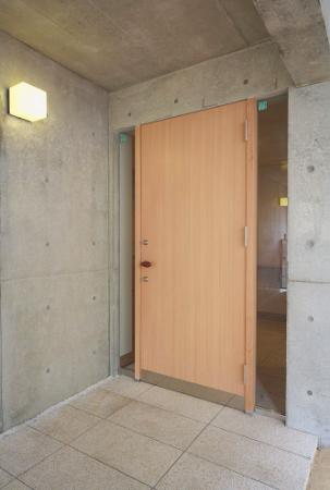 『坂の家』柔らかでナチュラルな住まい (明るい木目の玄関ドア)