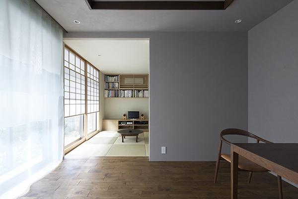 『二子新地の家』雪見障子越しに庭を眺める住まいの部屋 茶の間を見る