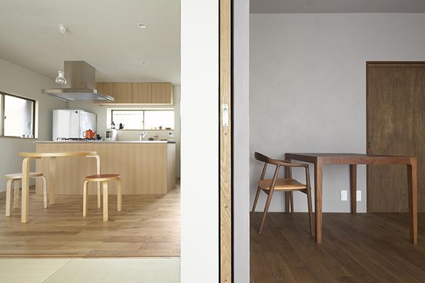 『二子新地の家』雪見障子越しに庭を眺める住まいの部屋 木目の色調が異なる2部屋