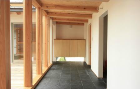 『多賀城のコートハウス』中庭を囲む2世帯住宅の写真 風を呼び込む地窓のある玄関土間