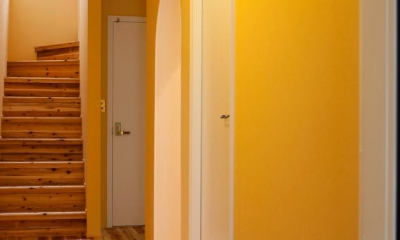 玄関ホール-壁のイエローと天井の柄クロス|東京都目黒区・斜天井にパイン材を貼り、涼やかな空間に