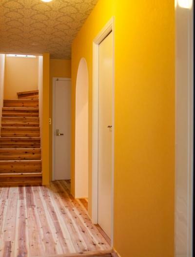 東京都目黒区・斜天井にパイン材を貼り、涼やかな空間に (玄関ホール-壁のイエローと天井の柄クロス)