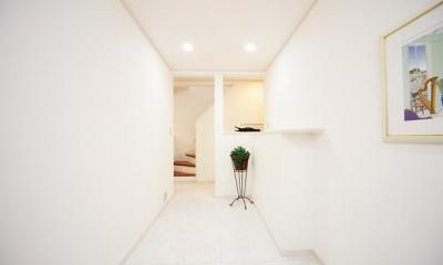 キッチンを中心に左右に広がるリビングダイニング (白で統一された廊下)