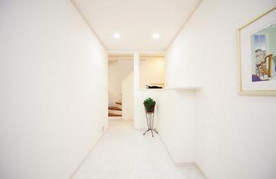 白で統一された廊下 (キッチンを中心に左右に広がるリビングダイニング)