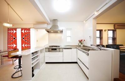 L型のオープンキッチン (キッチンを中心に左右に広がるリビングダイニング)