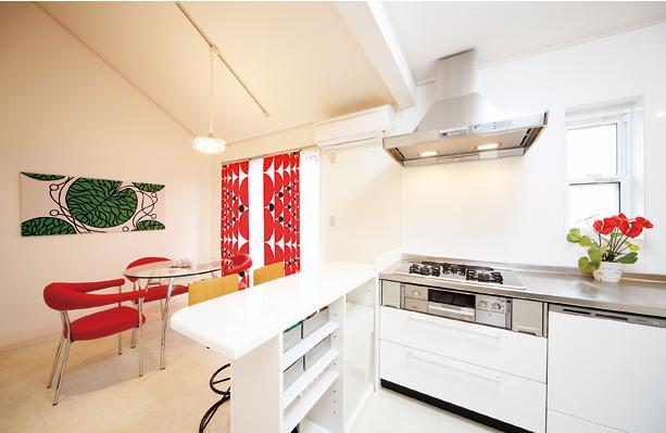 キッチンを中心に左右に広がるリビングダイニング (パステルカラーがアクセントのDK)