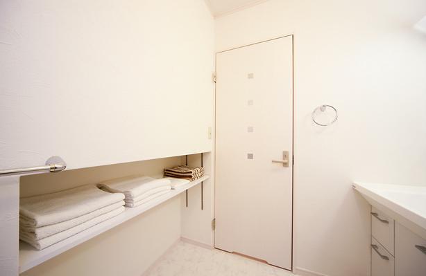 キッチンを中心に左右に広がるリビングダイニング (白で統一された脱衣所)