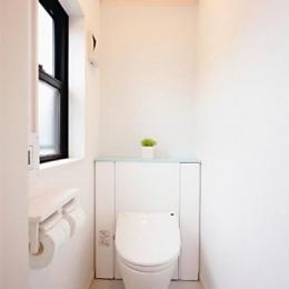 キッチンを中心に左右に広がるリビングダイニング (白で統一されたトイレ)
