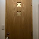 I邸・斜めに配置したキッチンで、動きと変化をの写真 クローバー柄を取り入れたタモ材のドア