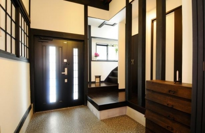 ダークな色合いの落ち着いた玄関 (日本情緒漂う「蔵」とシンプルモダンのLDK)