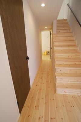 『海を望む家』建築家と建てる横須賀の狭小住宅の写真 パイン材による玄関・廊下・階段