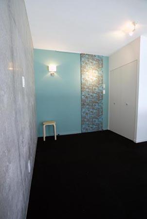 『collina』多様な価値感を受け入れるシンプルな箱の部屋 植物柄の壁紙がアクセントの寝室