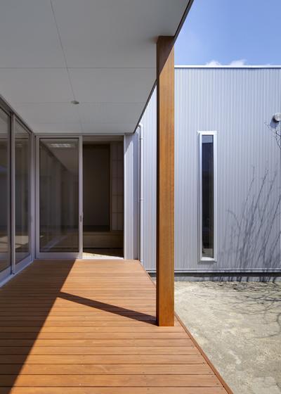 『公園前の家』明るくて風通しの良い住宅の部屋 日当たりのよいデッキ