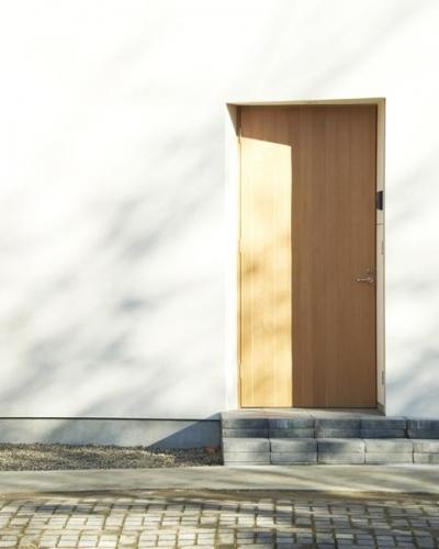 白い外壁に映える木製玄関ドア (木造町の離れ)