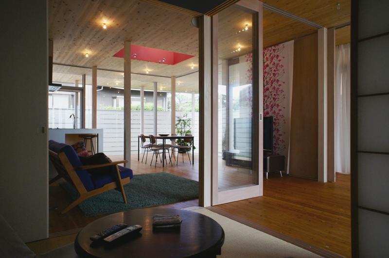 『菜園ののったフラット』3方向にひらいたコートハウスの部屋 和室よりLDKを見る