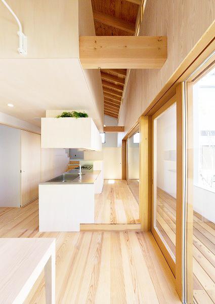 『コヤナカハウス』半屋外空間のドマがある家の写真 ダイニングよりキッチンを見る