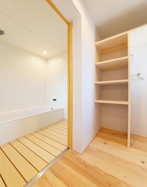 『コヤナカハウス』半屋外空間のドマがある家の写真 白と木目のコントラストが美しい浴室