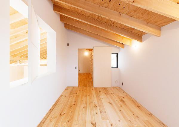 『コヤナカハウス』半屋外空間のドマがある家の部屋 室内窓のあるナチュラルな寝室