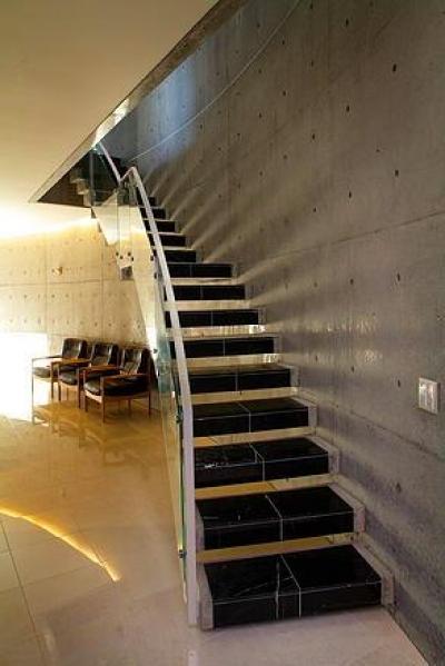 コンクリート打ち放し壁のクールな階段 (『N Residence』柔らかな光に満たされた二世帯住宅)