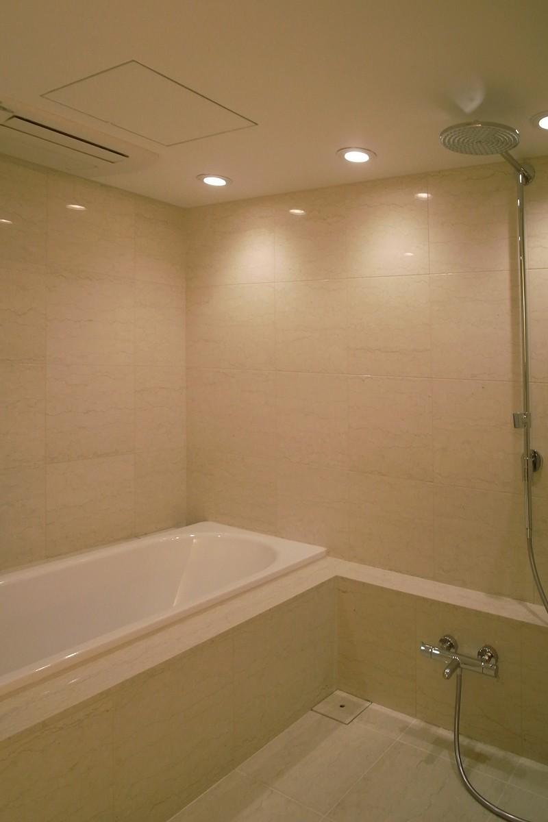 あたたかみある素材と照明の写真 レインシャワーのバスルーム