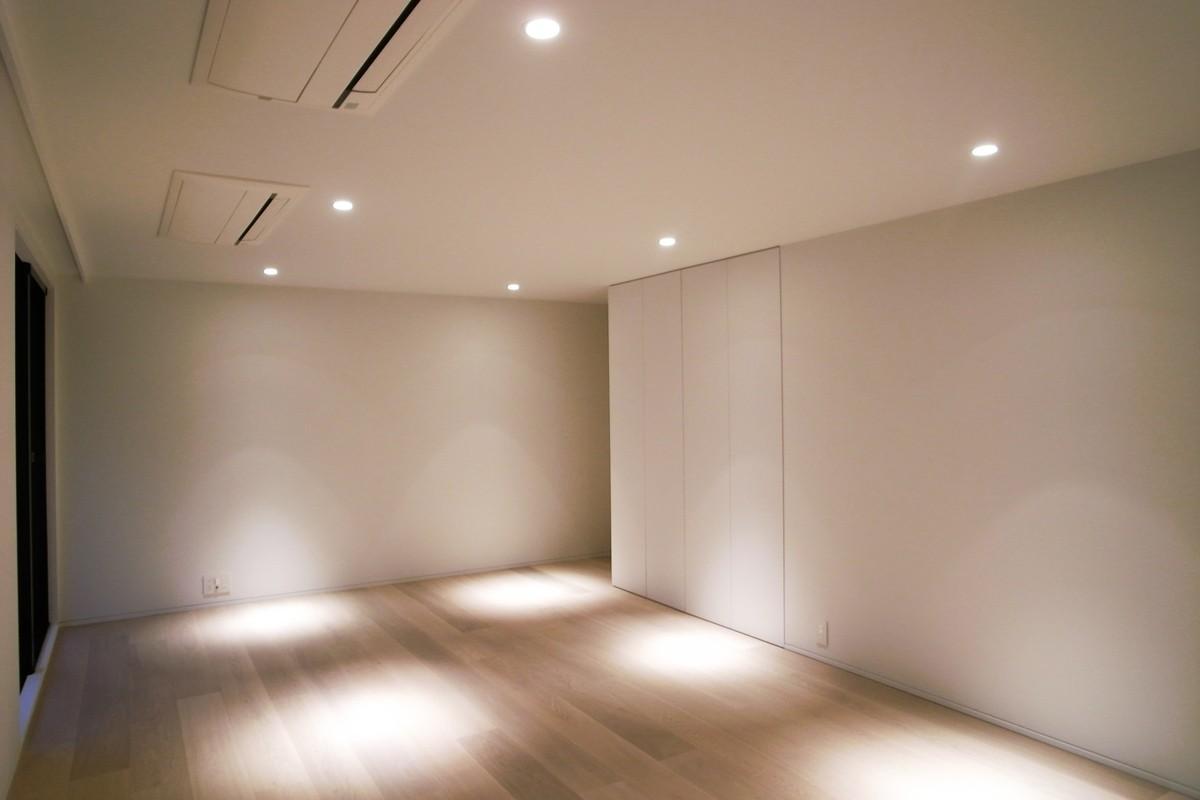 あたたかみある素材と照明の写真 スポットライトが明るく照らす寝室