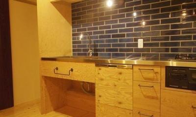 アイアンの取っ手のオリジナルキッチン|コンクリート現し天井と珪藻土壁のある家