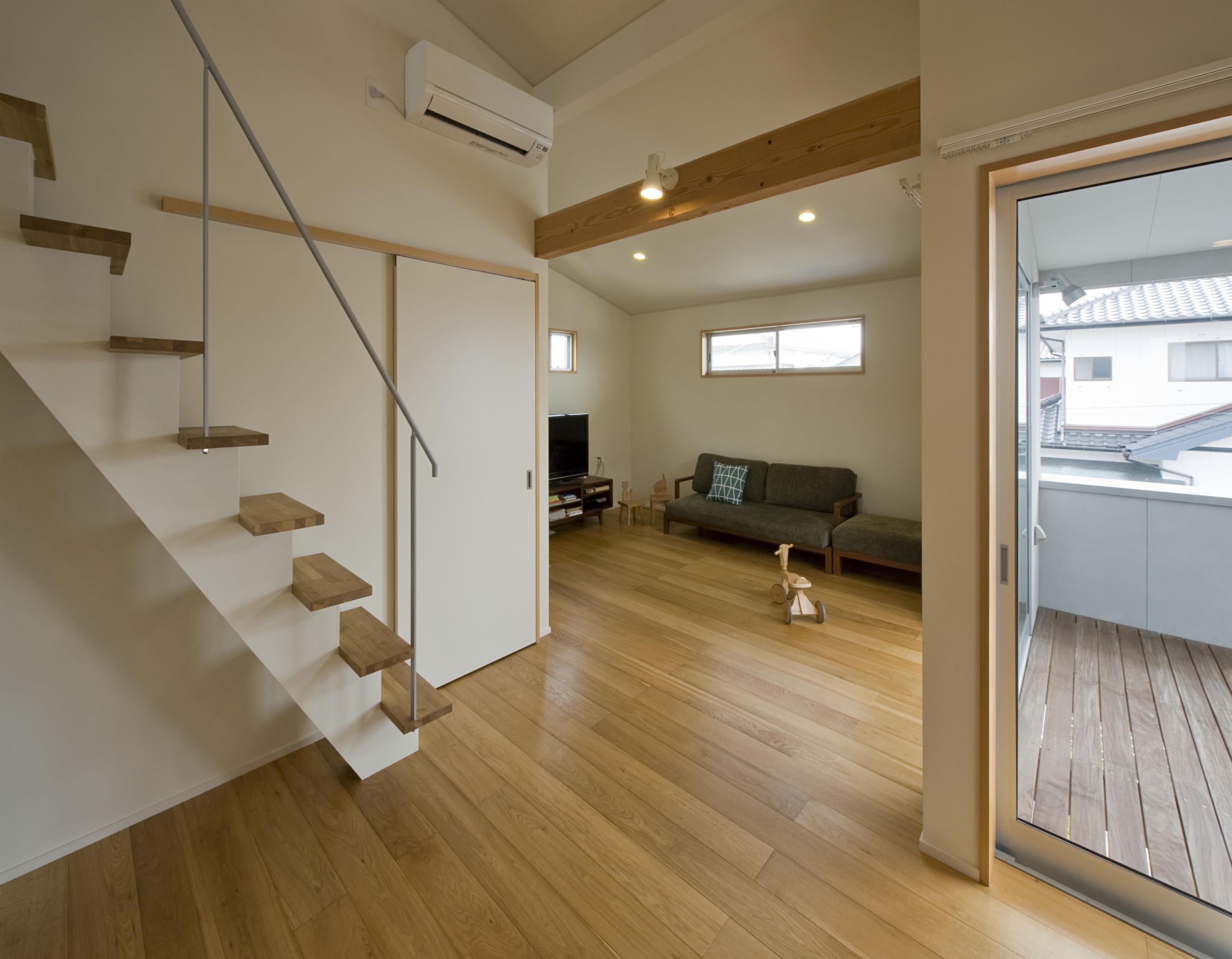 2階が生活拠点のシンプルな家の写真 ダイニングからリビングを見る