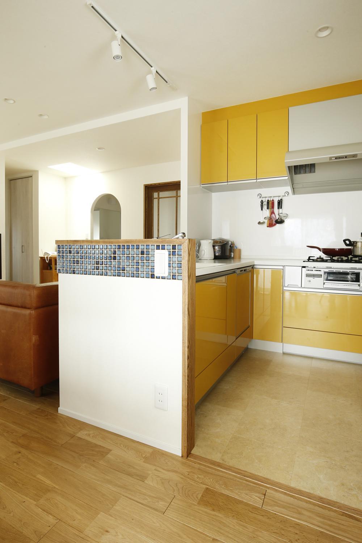K邸・小さな個室と大きなリビング、心地のよい暮らし方の写真 ビタミンカラーのL字型対面式キッチン