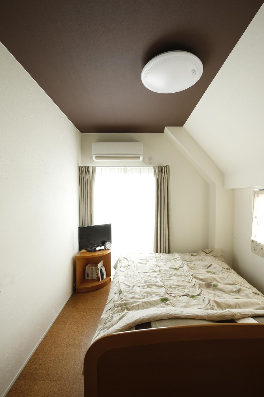 K邸・小さな個室と大きなリビング、心地のよい暮らし方の写真 天井がダークブラウンの落ち着いた寝室