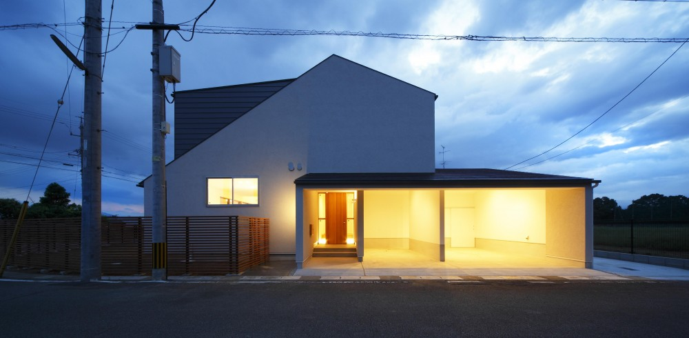 おおきな屋根を楽しむ住まい (ビルトインガレージのある外観、夜景)