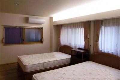 枕元のカーテンボックス上部は間接照明 (江東の住宅)