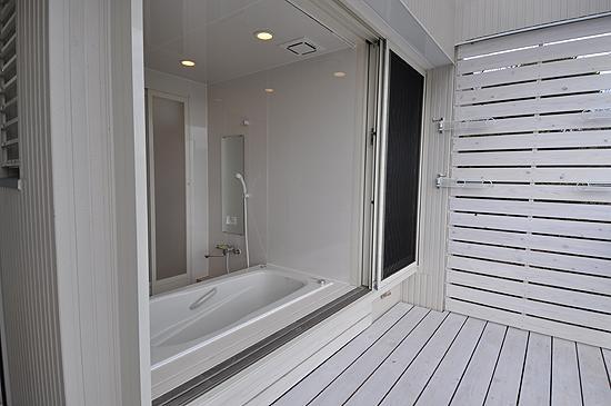 白いウッドデッキの家の写真 フルオープンサッシの浴室とバスコート