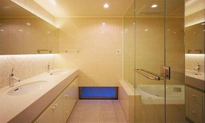 ダブルボウルの洗面コーナーとガラス張りのバスルーム|川西町の家