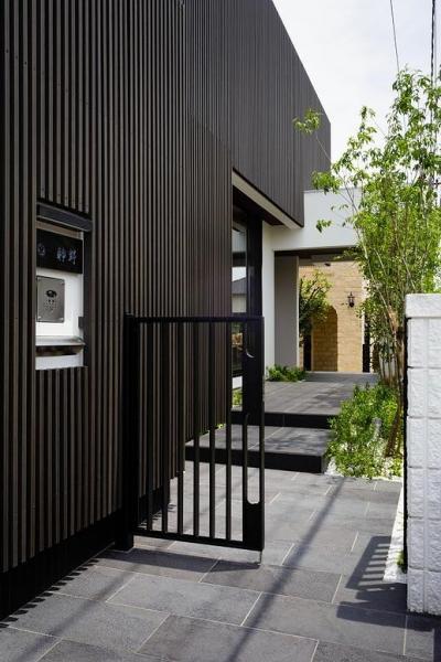 門扉からエントランスに続くタイル張りの庭 (CAT HOUSE (猫と暮らす家))
